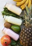 Fruktsmoothies av olika smaker i exponeringsglas skorrar med ingredienser på vit träbakgrund Bästa sikt, från över Lekmanna- läge fotografering för bildbyråer