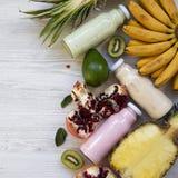 Fruktsmoothies eller milkshakar av olika färger i glasflaskor med tropiska frukter på vit träyttersida, över huvudet sikt från royaltyfri foto