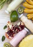 Fruktsmoothies eller milkshake av olika f?rger i exponeringsglaskrus med f?rgrika frukter p? vit tr?bakgrund, b?sta sikt Fr?n ?ve arkivbild