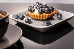 Frukttartleten p? en platta och en kopp kaffe p? tabellen, frukt bakade skalet, fruktmuffin med b?ret royaltyfri fotografi