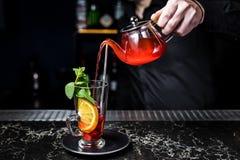 Fruktte med tranbär, tekannan och exponeringsglas, mörk bakgrund royaltyfria foton