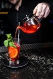 Fruktte med tranbär, tekannan och exponeringsglas, mörk bakgrund royaltyfri foto