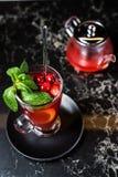 Fruktte med tranbär, tekannan och exponeringsglas, mörk bakgrund royaltyfri bild