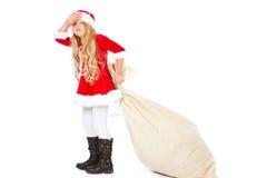 Fräulein Sankt erschöpft vom Ziehen des schweren Geschenksacks Stockfotografie