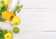 Frullati con i peperoni, mela, limone, prezzemolo in barattoli di vetro su un fondo di legno Fotografie Stock