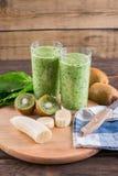 Frullati dalla banana, dagli spinaci e dal kiwi su una tavola di legno Fotografia Stock