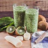 Frullati dalla banana, dagli spinaci e dal kiwi su una tavola di legno Fotografie Stock