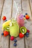 Frullati mescolati freschi della frutta in bottiglie per il latte d'annata Fotografie Stock Libere da Diritti