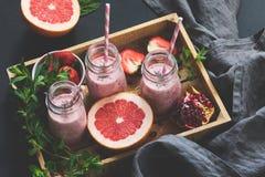 Frullati rosa della frutta in bottiglia Frullati del pompelmo, del melograno e della fragola immagini stock