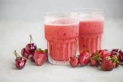 Frullati rossi delle bacche con i frutti delle ciliege e delle fragole Fotografia Stock