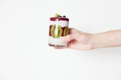 Frullati in un vetro in una mano su un fondo bianco con berrie fotografia stock libera da diritti