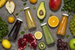 Frullati variopinti in bottiglie con frutta e le verdure tropicali fresche su fondo concreto, vista superiore Disposizione piana immagine stock