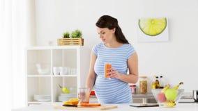 Frullato bevente della frutta della donna incinta a casa stock footage