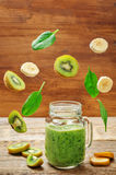 Frullato degli spinaci della banana del kiwi con i pezzi volanti Fotografia Stock