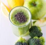 Frullato dei broccoli in ciotola di vetro su fondo di legno bianco con il limone e la mela Fotografie Stock Libere da Diritti