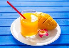 Frullato del mango in un vetro/vetro e mango su un fondo blu Scossa del mango Immagini Stock