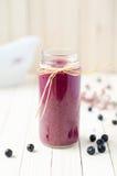 Frullato del ribes nero e del mirtillo rosso in barattoli di vetro su un wo bianco Fotografia Stock