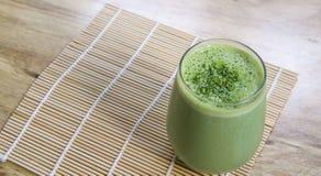 Frullato del tè verde di Matcha in vetro sulla stuoia di bambù sulla tavola Immagine Stock