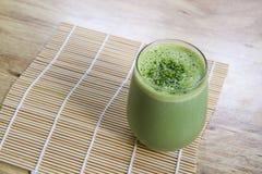 Frullato del tè verde di Matcha in vetro sulla stuoia di bambù sulla tavola Fotografia Stock