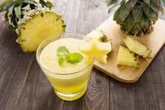 Frullato dell'ananas con l'ananas fresco sulla tavola di legno Fotografie Stock