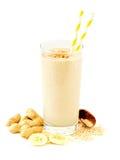 Frullato dell'avena della banana del burro di arachidi con gli ingredienti sparsi sopra bianco Fotografie Stock