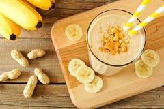 Frullato dell'avena della banana del burro di arachidi con le paglie, su legno Immagini Stock Libere da Diritti