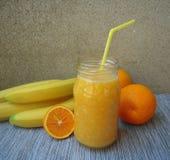 Frullato della banana con succo d'arancia Fotografie Stock Libere da Diritti