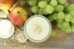 Frullato della prima colazione della farina d'avena con l'uva, la pera ed il yogurt nella vista superiore Fotografia Stock Libera da Diritti