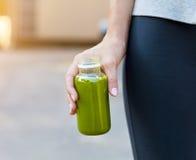 Frullato di verdure bevente della donna dopo l'allenamento corrente di forma fisica Fotografia Stock