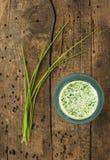 Frullato estivo della erba cipollina su vecchio legno in ciotola verde Immagini Stock