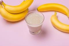 Frullato fatto fresco della banana in un vetro su fondo rosa immagini stock libere da diritti
