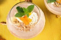 Frullato fruttato in vetro del dessert su un fondo giallo Cocktail con le albicocche secche, il gelato e le banane, vista superio immagini stock libere da diritti