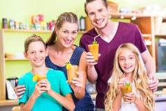 Frullato o succo bevente della famiglia in cucina domestica Immagine Stock