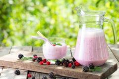 Frullato o yogurt della bacca in una brocca ed in un vetro con la menta e il berrie immagine stock
