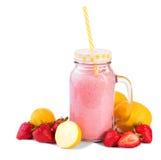 Frullato rosa naturale delizioso in un barattolo di vetro chiuso con i limoni e le fragole freschi intorno, isolato su un fondo b Immagine Stock