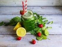 Frullato verde con spinaci e la fragola in vetro Immagine Stock