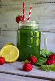 Frullato verde con spinaci e la fragola in vetro F selettiva Immagini Stock