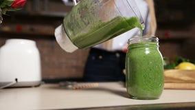Frullato verde fresco di versamento dal miscelatore nel barattolo stock footage