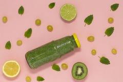 Frullato verde variopinto in bottiglia su fondo rosa, vista superiore immagini stock