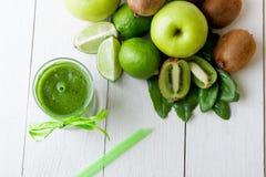 Frullato verde vicino agli ingredienti per su fondo di legno bianco Apple, calce, spinaci detox Bevanda sana Vista superiore Immagine Stock