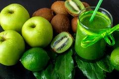 Frullato verde vicino agli ingredienti per su fondo di legno nero Apple, calce, spinaci, kiwi detox Bevanda sana Immagini Stock Libere da Diritti