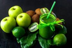 Frullato verde vicino agli ingredienti per su fondo di legno nero Apple, calce, spinaci, kiwi detox Bevanda sana Alimento puro Immagine Stock Libera da Diritti