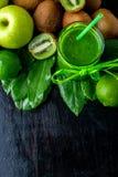 Frullato verde vicino agli ingredienti per su fondo di legno nero Apple, calce, spinaci, kiwi detox Bevanda sana Vista superiore  Immagine Stock