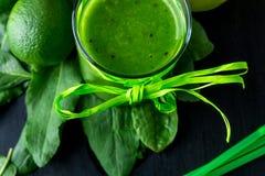 Frullato verde vicino agli ingredienti per su fondo di legno nero Calce, spinaci detox Bevanda sana Vista superiore Fotografia Stock Libera da Diritti