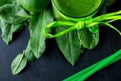 Frullato verde vicino agli ingredienti per su fondo di legno nero Calce, spinaci detox Bevanda sana Vista superiore Immagine Stock
