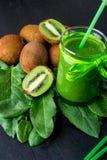 Frullato verde vicino agli ingredienti per su fondo di legno nero Kiwi e spinaci detox Bevanda sana Fotografie Stock