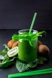 Frullato verde vicino agli ingredienti per su fondo di legno nero Kiwi e spinaci detox Bevanda sana Immagine Stock Libera da Diritti