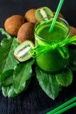 Frullato verde vicino agli ingredienti per su fondo di legno nero Kiwi e spinaci detox Bevanda sana Fotografia Stock