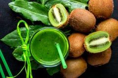 Frullato verde vicino agli ingredienti per su fondo di legno nero Kiwi e spinaci detox Bevanda sana Vista superiore Fotografia Stock