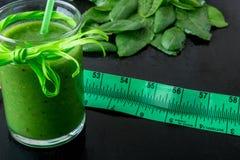 Frullato verde vicino al centimetro ed ingredienti per su fondo di legno nero Dieta detox Bevanda sana Fotografia Stock Libera da Diritti
